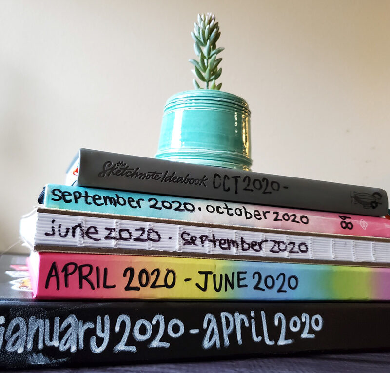 Stack of finished sketchbooks with dates on the spines