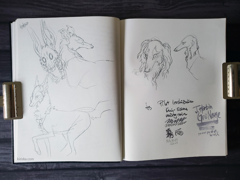 Open sketchbook with random dog sketches, a bunny monster, and ink tests.